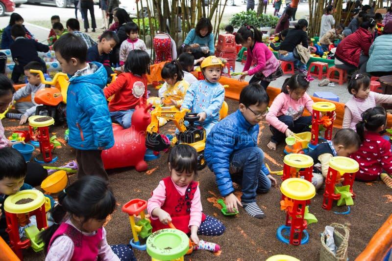 Asiatische Kinder, die mit Spielwaren auf einem Spielplatz spielen stockfoto