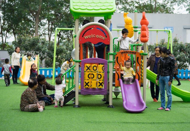 Asiatische Kinder, die mit Spielwaren auf einem Spielplatz spielen lizenzfreies stockfoto