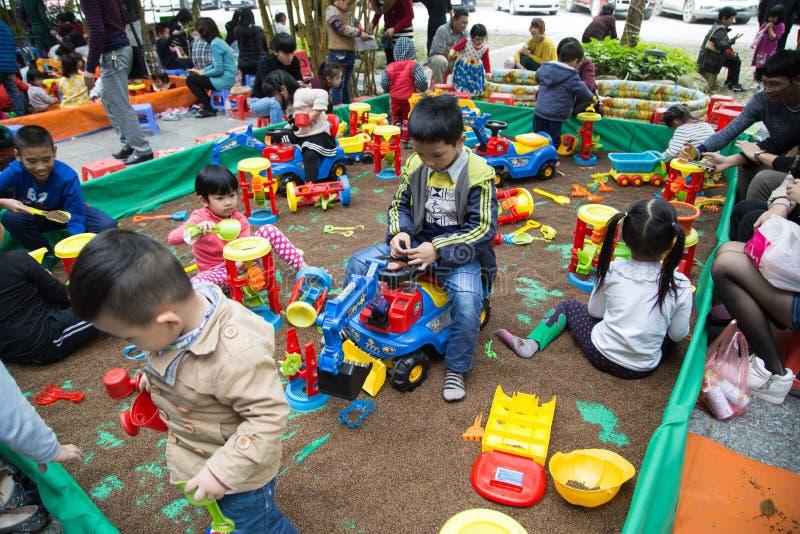 Asiatische Kinder, die mit Spielwaren auf einem Spielplatz spielen lizenzfreies stockbild