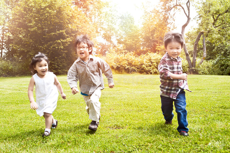 Asiatische Kinder, die in Park laufen lizenzfreie stockbilder