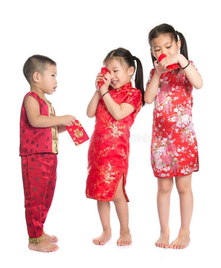 Asiatische Kinder, die in rotes Paket spähen stockfotografie