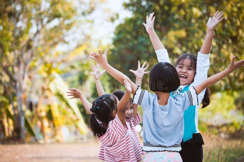 Asiatische Kinder heben Hände und das Spielen zusammen mit Spaß an lizenzfreies stockbild