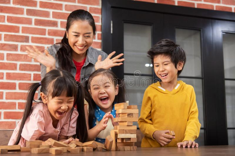 Asiatische Kinder und ihr Lehrer spielen Holzklotzstapel gam stockbild