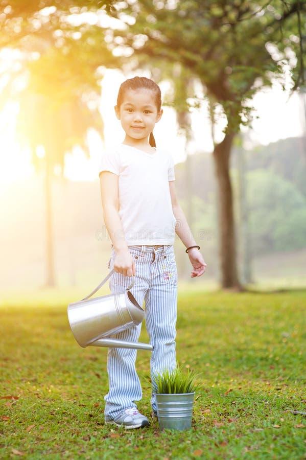 Asiatische Kinderbewässerungsanlage draußen lizenzfreies stockbild