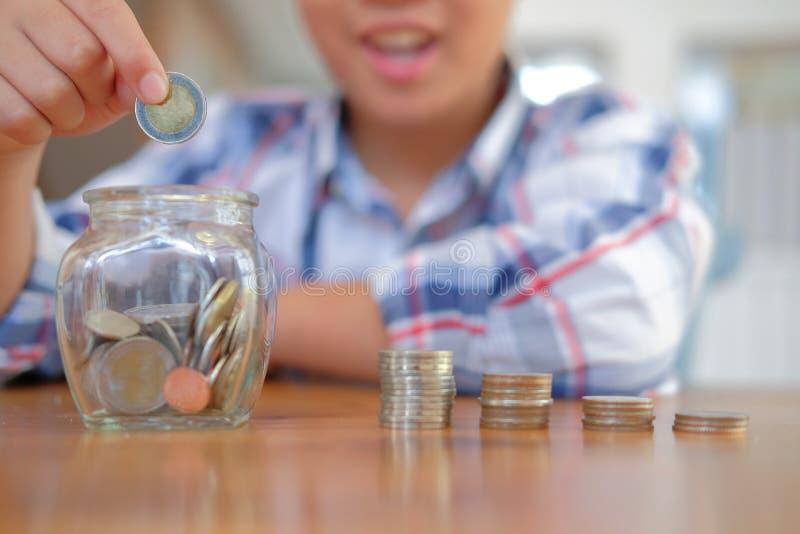 asiatische Kinderjungen-Kinderkinder mit Münzenstapelglas nachfolgende Geldmünzen lokalisierten Beschneidungspfad lizenzfreie stockfotos