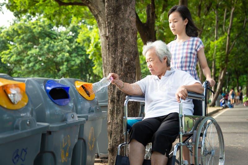Asiatische kleine Mädchen oder Enkelin, ältere Großmutter, die Plastikflasche in die Recycling-Mülltonne packt, ältere Touristen lizenzfreies stockfoto