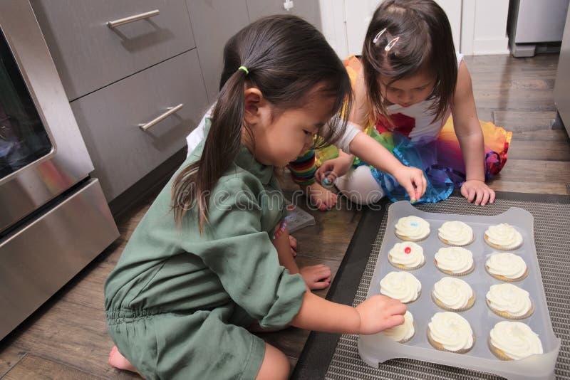 Asiatische Kleinkinder, die kleine Kuchen in der Küche verzieren lizenzfreies stockfoto