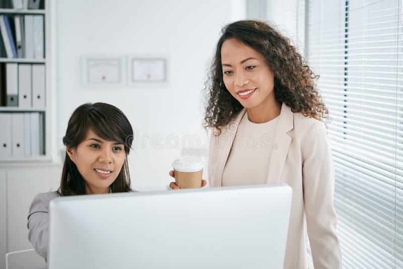 Asiatische Kollegen eingewickelt oben in der Arbeit stockbilder
