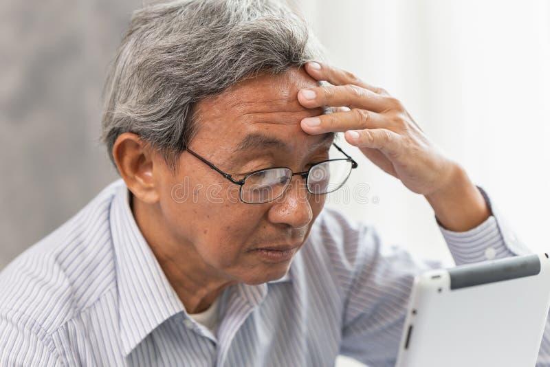 Asiatische Kopfschmerzen Gläser des alten Mannes von der Anwendung und vom Schauen des Tablettenschirmes stockbild