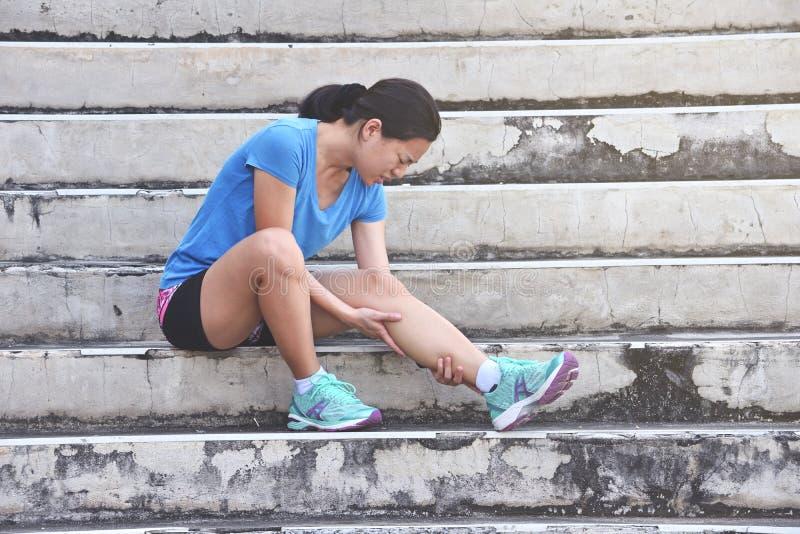 Asiatische Läuferfrau, die Knieschmerz und -problem nach laufend hat stockbilder