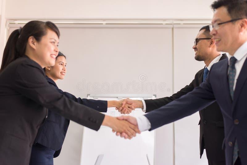 Asiatische Leute des Geschäftsteams im Gesellschaftsanzug, der die Hände oben beenden Sitzung, selektiven Fokus, glückliche Partn lizenzfreie stockfotos