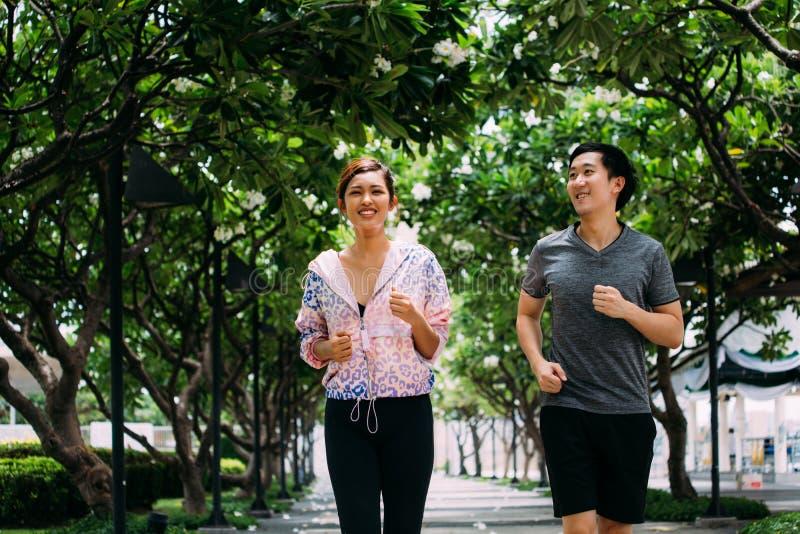 Asiatische Leute, die in Park laufen lizenzfreie stockfotos