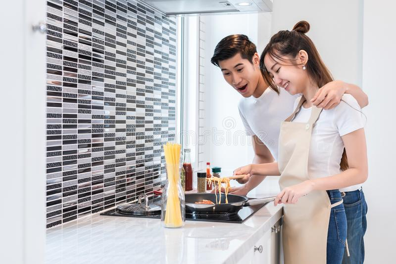 Asiatische Liebhaber oder Paare, die Abendessen im Küchenraum kochen Mannpunkt zur köstlichen Nahrung die Frauenherstellung Feier lizenzfreie stockbilder