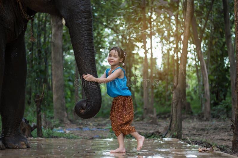 Asiatische Mädchen, die mit Elefanten spielen lizenzfreie stockbilder
