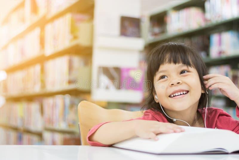 Asiatische Mädchen sind Lesebücher und Hören Musik lizenzfreie stockbilder