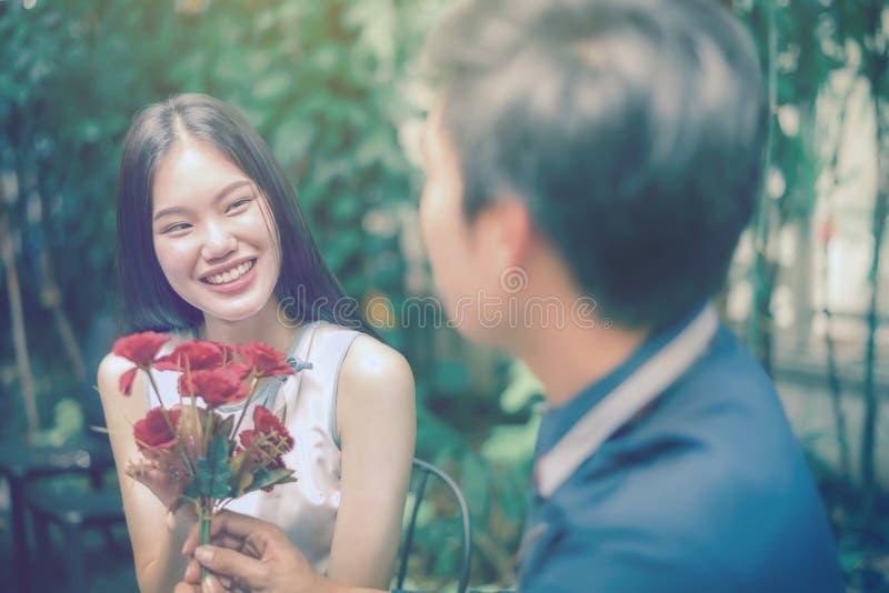 Asiatische Mädchen werden mit den roten Blumen erfreut, die vom Mann empfangen werden, den sie liebte stockfotografie