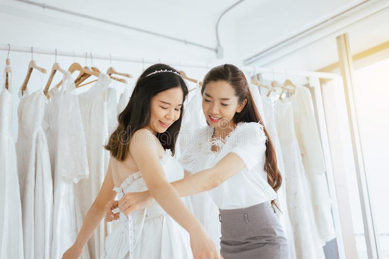 Asiatische Mädchenbraut, die auf Hochzeitskleid, Frauendesigner vornimmt Anpassung mit messendem Band versucht stockfotos