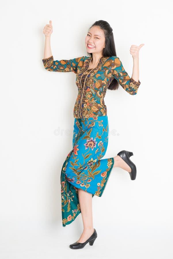 Asiatische Mädchendaumen up und herum springend stockfotos