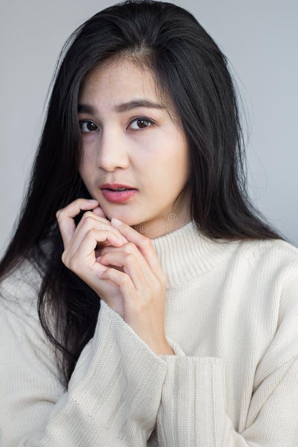 Asiatische Mädchenhaltungen behandeln ihr Kinn stockfotos