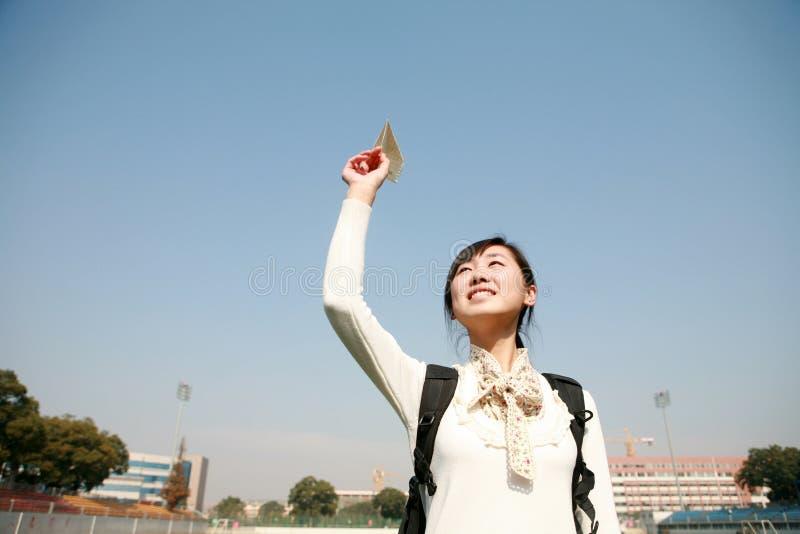 Asiatische Mädchenholding-Papierflugzeuge lizenzfreie stockfotos