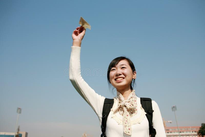 Asiatische Mädchenholding-Papierflugzeuge stockbild