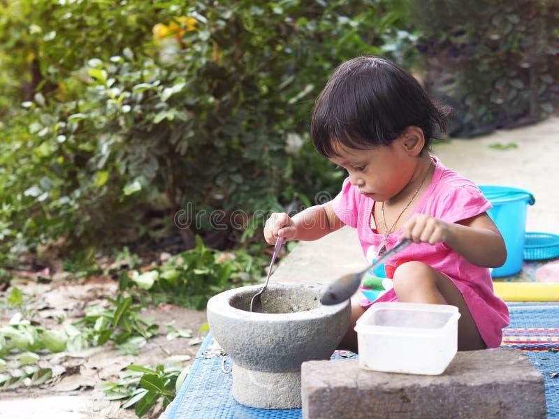 Asiatische Mädchenkinder spielen das Kochen mit Mörser stockfotografie