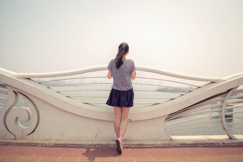 Asiatische Mädchenrückseite in einem Küstengeländer lizenzfreies stockbild