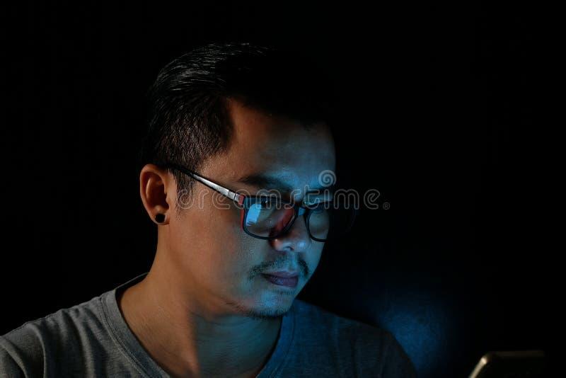 Asiatische Männer benutzen das Telefon oder die Tablette mit einem Blaulicht in der Dunkelheit, lizenzfreie stockfotos
