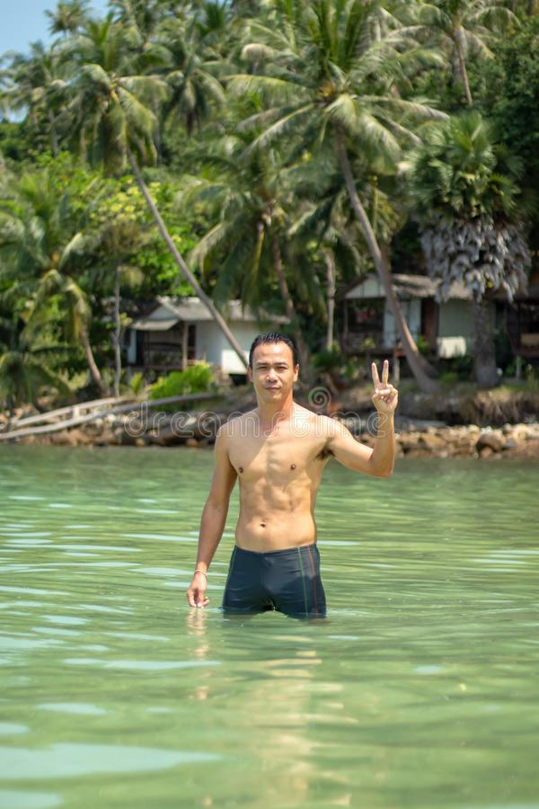 Asiatische Männer, die in den Seehintergrundfelsen und -bäumen schwimmen stockbilder