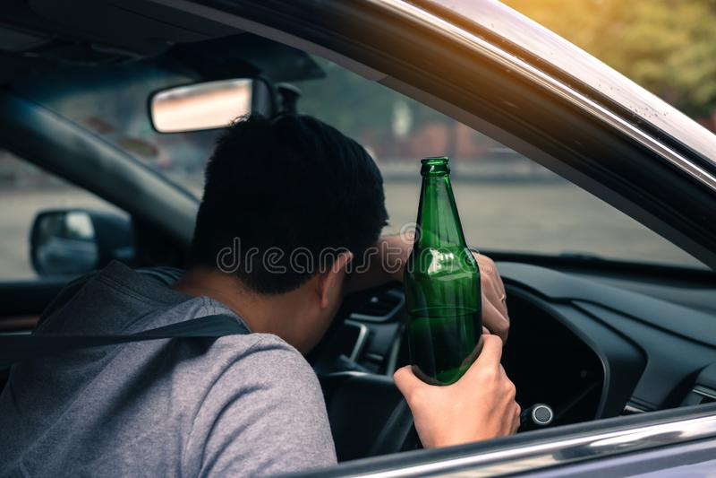 Asiatische Männer trinken viel Alkohol, bis er bewusstlos nicht nach Hause fahren kann und am Lenkrad schlafen kann lizenzfreie stockbilder