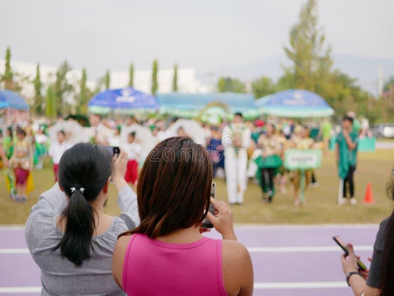 Asiatische Mütter, die Fotos ihrer Kinder in der Schule teilnehmen an einem Sporttagesereignis aufpassen und machen stockbild