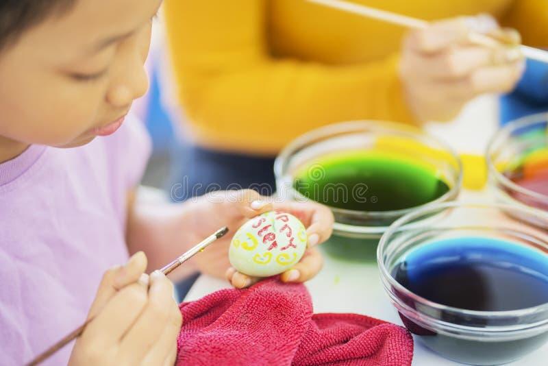 Asiatische malende Eier des kleinen Mädchens mit ihrer Mutter stockfotografie