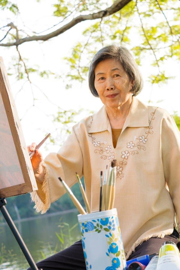 Asiatische Malerei der alten Frau lizenzfreie stockbilder
