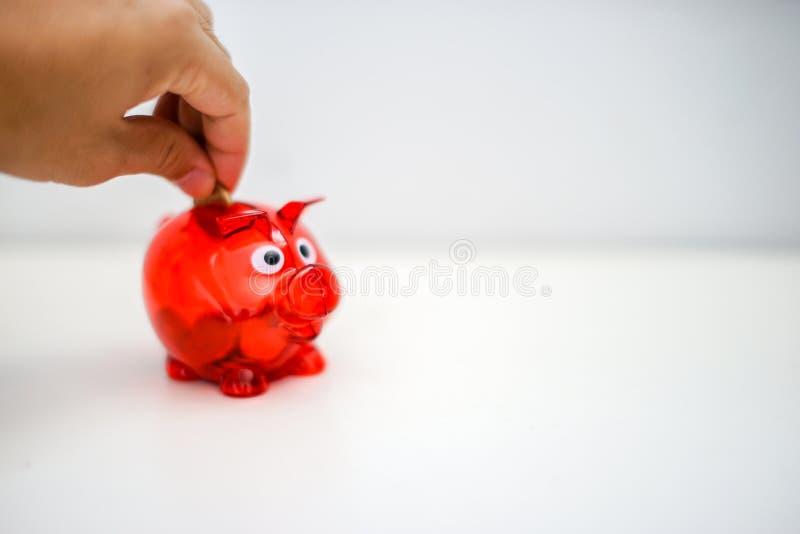 Asiatische Mann Hand, die Münze in rotes Sparschwein setzt stockfoto
