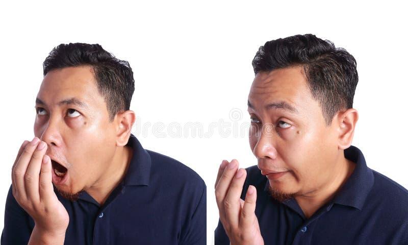 Asiatische Mann-Kontrolle sein eigener Mund-Geruch stockfotografie