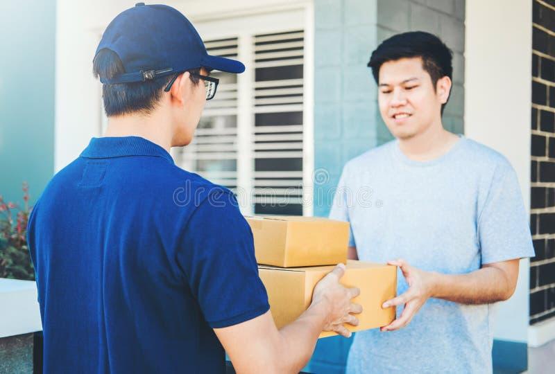 Asiatische Mannhand, die zu Hause Kästen einer Lieferung vom Berufslieferboteen annimmt lizenzfreies stockfoto
