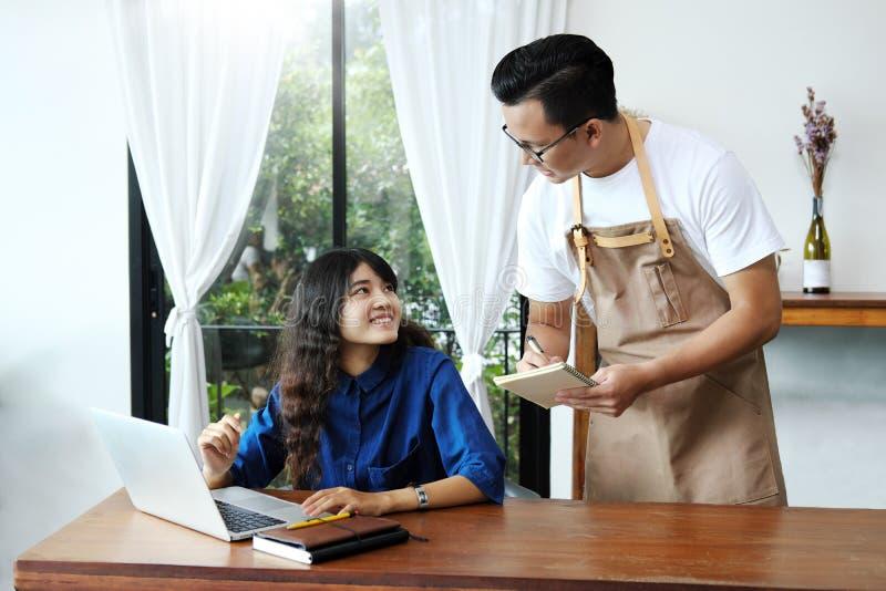 Asiatische Mannkellnerin, die Bestellung der Frau im Café entgegennimmt Café resta lizenzfreie stockfotos