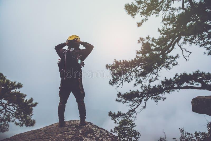 Asiatische Mannreisenatur Reise entspannen sich Stehen Sie oben Landschaften auf der Klippe Bei Sonnenaufgang, der hat, Schutz ei stockfoto