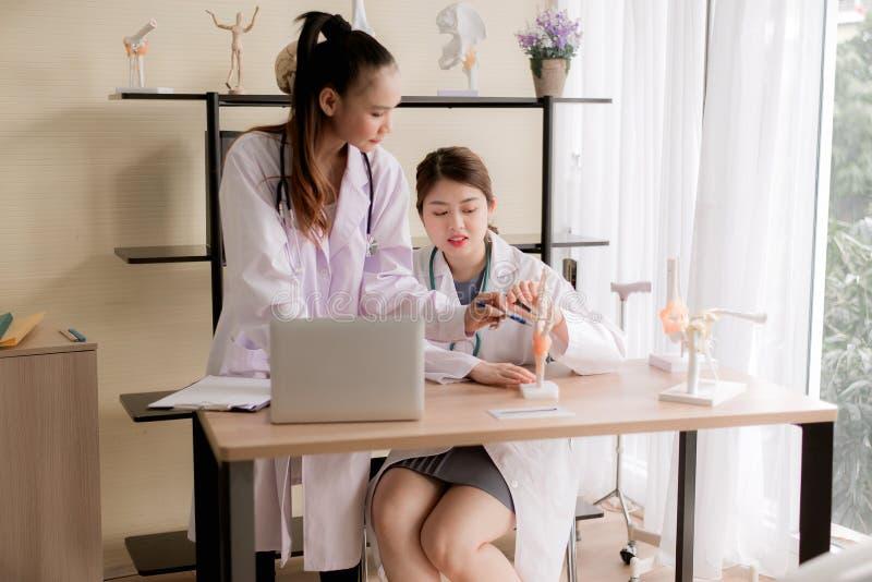 Asiatische Medizinstudentfrauenausbildung und Skeletthandmodell am Krankenhaus zusammen verwenden lizenzfreie stockfotos