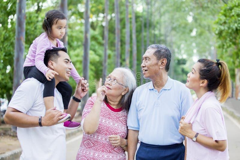 Asiatische multi Generationsfamilie, die im Park plaudert stockbild