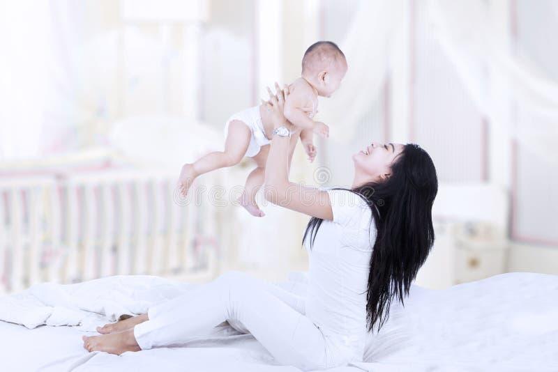 Asiatische Mutter, die ein Baby anhebt lizenzfreie stockfotos