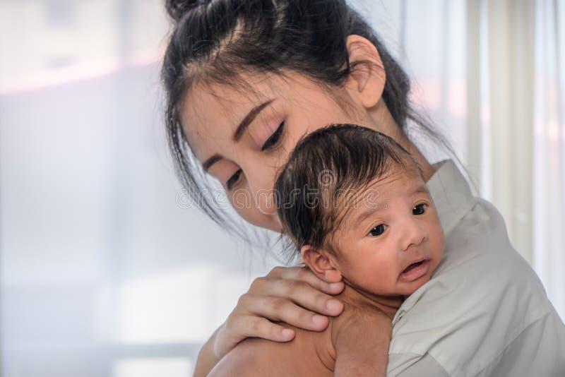 Asiatische Mutter, die ihr nettes Säuglingsbaby auf ihrer Schulter hält stockfotos