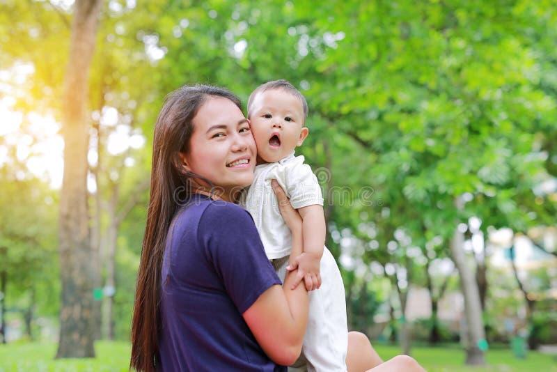 Asiatische Mutter, die ihr Säuglingsbaby im Sommergarten trägt stockbild