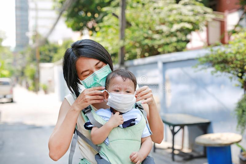 Asiatische Mutter, die ihr S?uglingsbaby durch das hipseat im Freien mit dem Tragen einer Schutzmaske gegen P.M. 2 tr?gt 5 Luftve stockfoto