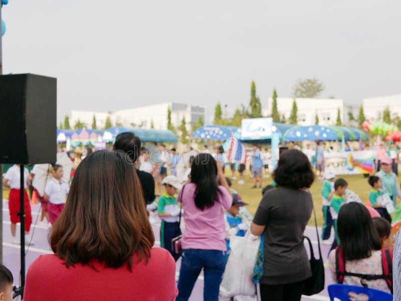 Asiatische Mutter, die ihre Kinder aufpasst, an einem Sporttagesereignis in der Schule teilzunehmen lizenzfreie stockbilder