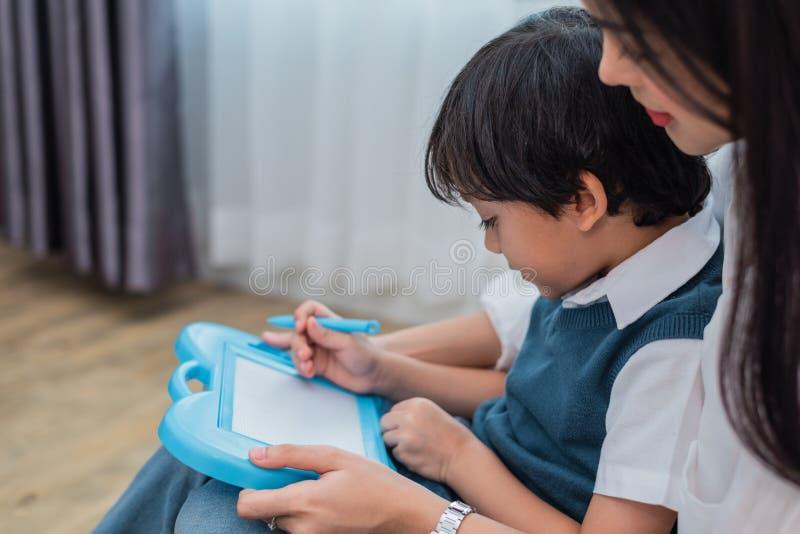 Asiatische Mutter, die netten Jungen zu in Tafel zusammen zeichnen unterrichtet Zur?ck zu Schule und Bildungskonzept Familie und  lizenzfreie stockfotografie