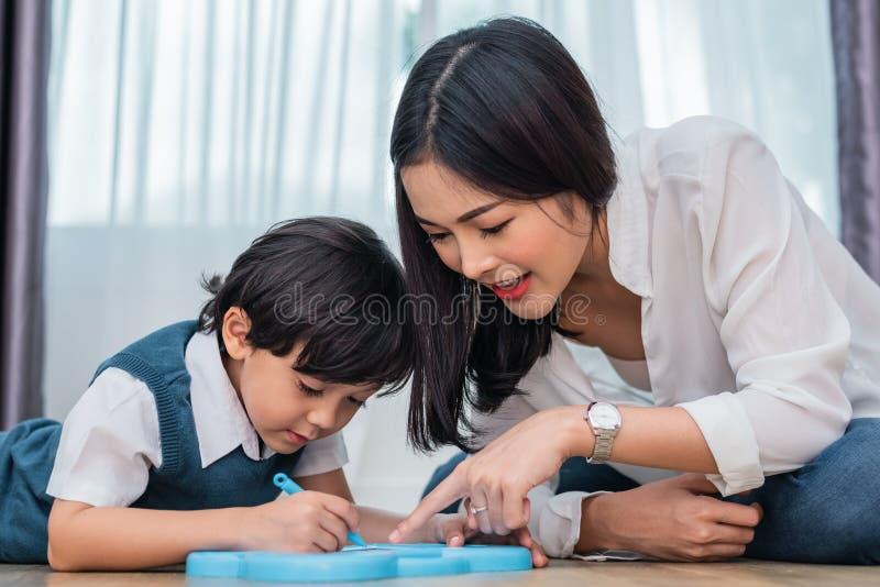 Asiatische Mutter, die netten Jungen zu in Tafel zusammen zeichnen unterrichtet Zur?ck zu Schule und Bildungskonzept Familie und  stockfotos