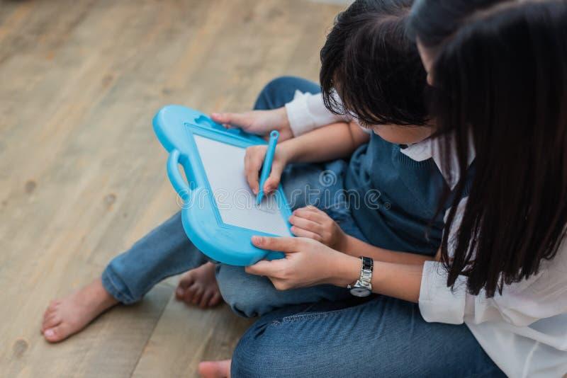 Asiatische Mutter, die netten Jungen zu in Tafel zusammen zeichnen unterrichtet Zur?ck zu Schule und Bildungskonzept Familie und  stockfoto