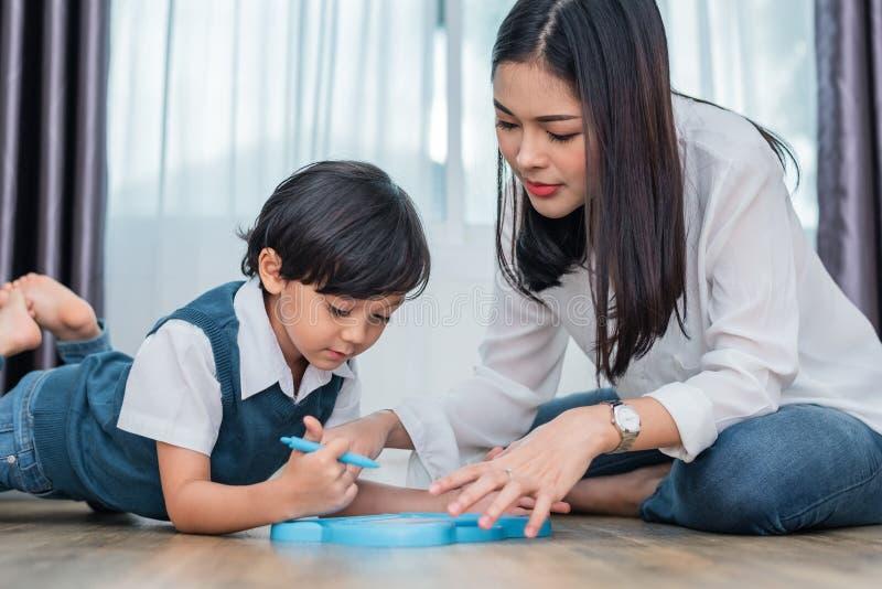 Asiatische Mutter, die netten Jungen zu in Tafel zusammen zeichnen unterrichtet Zur?ck zu Schule und Bildungskonzept Familie und  stockbilder