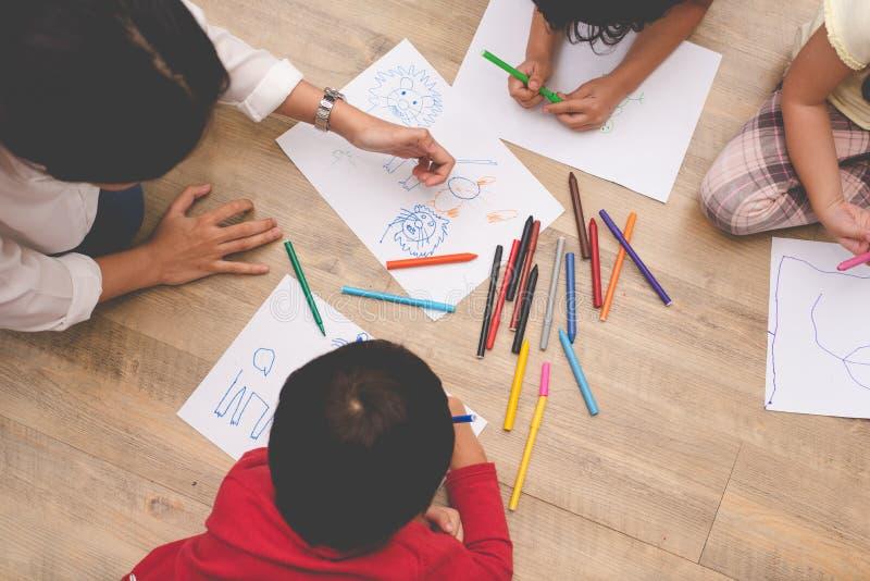 Asiatische Mutter, die vier kleine Kinder zu zeichnender Karikatur im Kunstunterricht mit Farbstift unterrichtet Zur?ck zu Schule lizenzfreies stockfoto